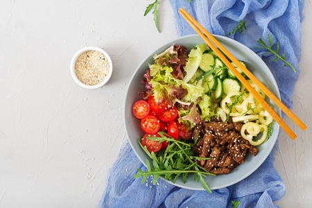 Salad with beef teriyaki and fresh vegetables - tomatoes, cucumbers, paprika, arugula and lettuce in bowl. Flat lay. Top view Stock Photo - 82112287