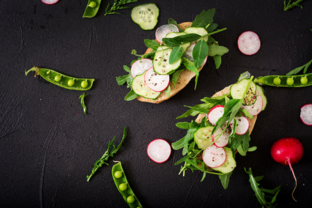 meatless: Vegetarian sandwiches with cucumber, radish, arugula and green peas. Flat lay. Top view Stock Photo