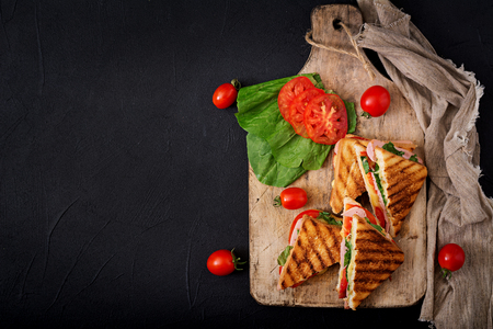 Club sandwich panini with ham, tomato, cheese and basil. Flat lay. Top view 스톡 콘텐츠