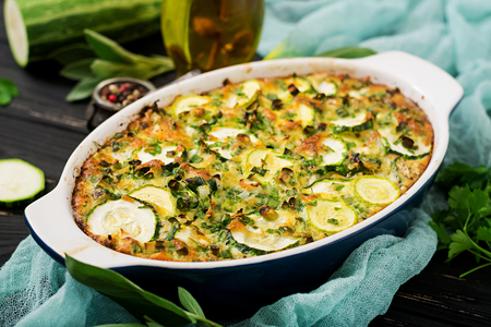 Zucchini casserole with eggs, milk, cheese and greens herbs 免版税图像