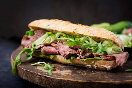 Sandwich of whole wheat bread with roast beef, cucumber and arugula
