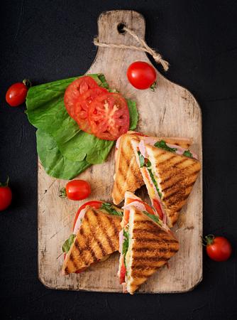 Sándwich de club de panini con jamón, tomate, queso y albahaca. Lay Flat. Vista superior Foto de archivo - 83441020