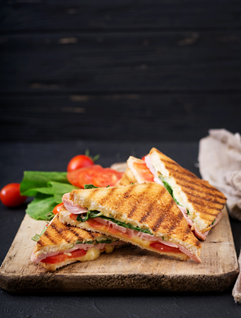 Club sandwich panini with ham, tomato, cheese and basil. Zdjęcie Seryjne - 83441030