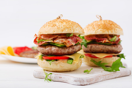 Big sandwich - hamburger burger with beef, cheese, tomato, cucumber and fried bacon. Stock Photo