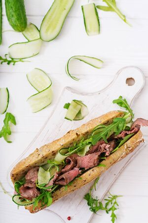 Sandwich of whole wheat bread with roast beef, cucumber and arugula. Top view. Flat lay Stock Photo