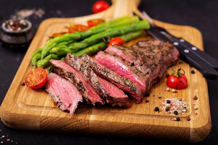 Filete jugoso carne rara con especias en una tabla de madera y guarnición de espárragos.