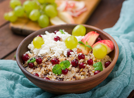 Delicious and healthy oatmeal with grapes, nuts, apples and cottage cheese. Healthy breakfast. Fitness food. Proper nutrition Stock Photo