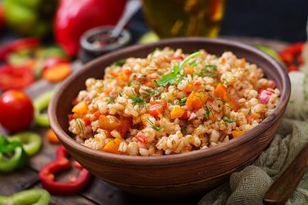 暗いバック グラウンドに野菜ベジタリアンもろいパール大麦のお粥 写真素材