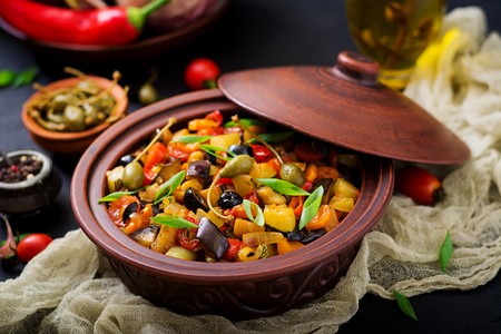 Hot spicy stew (caponata) eggplant, zucchini, sweet pepper, tomato, carrot, onion, olives and capers Stock Photo