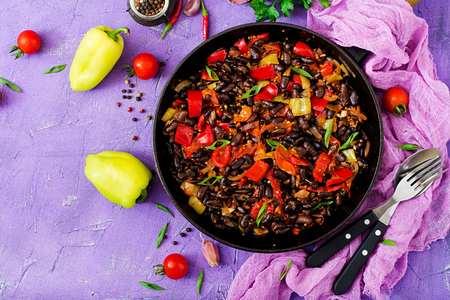 Stewed black beans with sweet peppers and tomatoes with spicy sauce in a pan. Flay lay. Top view Stock Photo