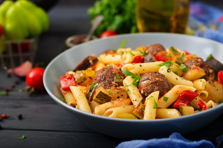 Penne pasta with meatballs in tomato sauce and vegetables in bowl