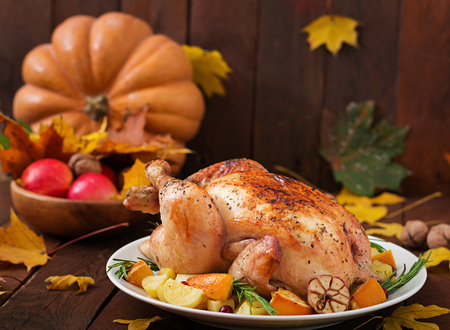 Roasted turkey garnished with cranberries on a rustic style table decorated with pumpkins, orange, apples and autumn leaf. Thanksgiving Day. Stock Photo