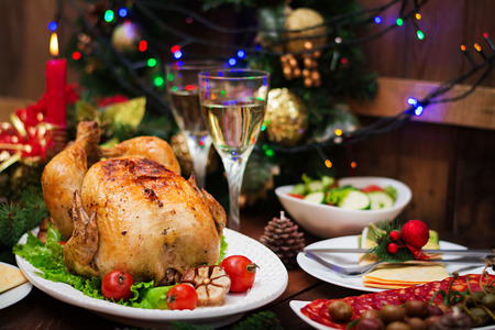 Baked turkey or chicken. The Christmas table is served with a turkey, decorated with bright tinsel and candles. Fried chicken, table. Christmas dinner.