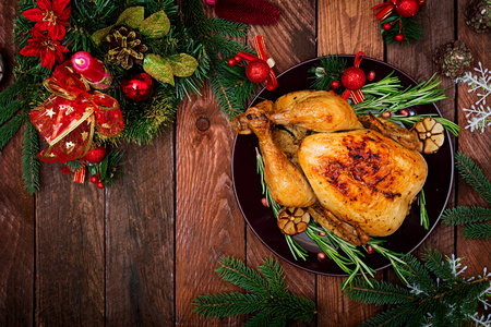 Baked turkey or chicken. The Christmas table is served with a turkey, decorated with bright tinsel and candles. Fried chicken, table. Christmas dinner. Flat lay. Top view Stockfoto