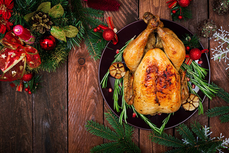 Baked turkey or chicken. The Christmas table is served with a turkey, decorated with bright tinsel and candles. Fried chicken, table. Christmas dinner. Flat lay. Top view Banco de Imagens