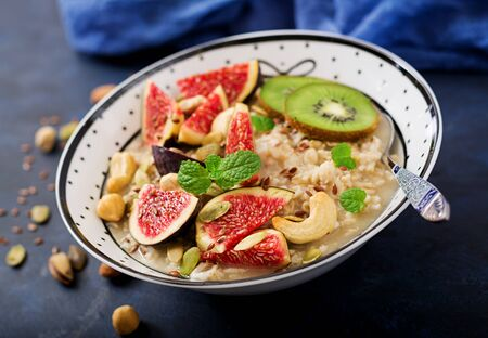 Delicious and healthy oatmeal with figs, nuts, kiwi and seeds. Healthy breakfast. Fitness food. Proper nutrition.