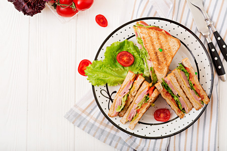 Club sandwich - panini with ham, cheese, tomato and herbs. Top view
