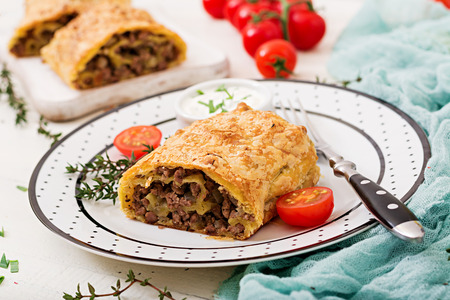 Appetizing strudel with minced beef, onions and herbs Stock Photo
