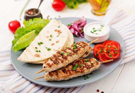 Minced Lula kebab grilled turkey (chicken) with fresh vegetables. 写真素材