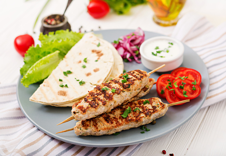 Minced Lula kebab grilled turkey (chicken) with fresh vegetables. Stock Photo