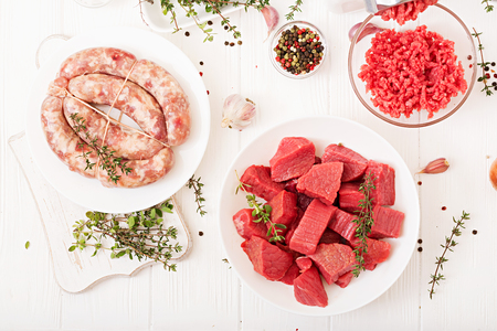 Chopped raw meat. The process of preparing forcemeat by means of a meat grinder. Homemade sausage. Ground beef. Top view