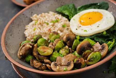 Healthy breakfast. Oat porridge, egg and salad of baked vegetables - mushrooms and Brussels sprouts. Healthy lifestyle.