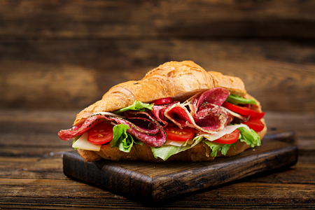 Tasty breakfast. Appetizing croissant with salami and, cheese and tomatoes