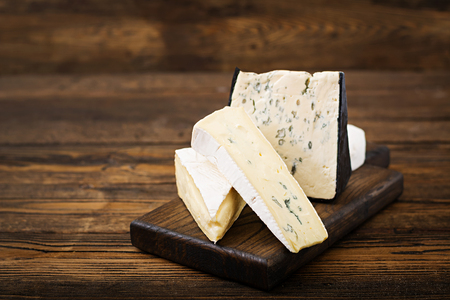 Assortment of cheeses. Camembert, dor blu, brie on a wooden background Stock Photo