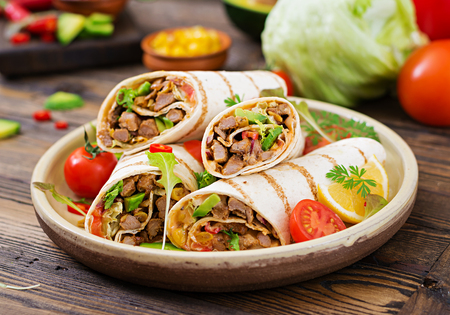 Burritos wraps with beef and vegetables on a wooden background. Beef burrito , mexican food. Healthy food background. Mexican cuisine.