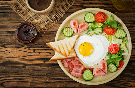 Breakfast on Valentines Day - fried egg in the shape of a heart, toasts, sausage, bacon and fresh vegetables. English breakfast. Cup of coffee. Top view