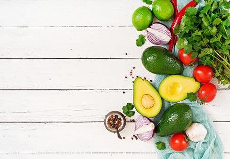 Guacamole sauce ingredients - avocado, tomato, onion, pepper chili, garlic, cilantro, lime on white background. Top view