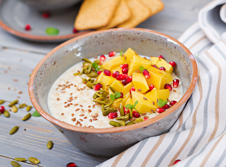 Tasty and healthy oatmeal porridge with mango, pomegranate and seeds. Healthy breakfast. Fitness food. Proper nutrition.