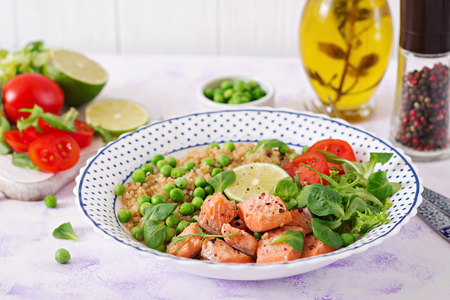 Healthy dinner. Slices of grilled salmon, quinoa, green peas, tomato, lime and lettuce leaves Stock Photo