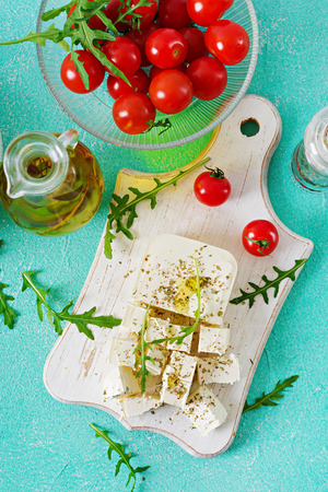 Feta cheese, cherry tomatoes and rucola on the table. Ingredients for salad. Top view Stock Photo