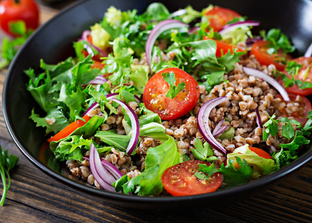 Buckwheat salad with cherry tomatoes, red onion and fresh herbs. Vegan food. Diet menu. Фото со стока