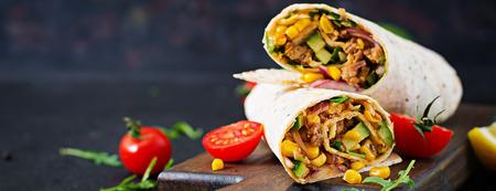 Burritos wickelt mit Rindfleisch und Gemüse auf schwarzem Hintergrund ein. Rindfleisch Burrito, mexikanisches Essen. Standard-Bild