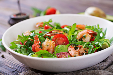 Fresh salad bowl with shrimp, tomato, avocado and arugula on wooden background close up. Healthy food. Clean eating.