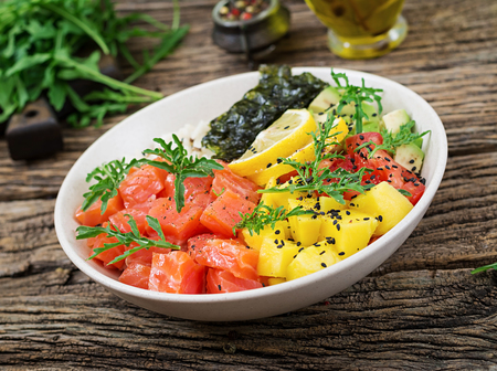 Hawaiian salmon fish poke bowl with rice, avocado, mango, tomato, sesame seeds and seaweeds. Buddha bowl. Diet food.