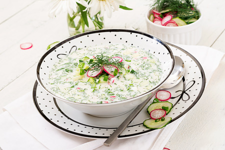 Cold soup with fresh cucumbers, radishes with yoghurt in bowl on wooden background. Traditional russian food - okroshka. Vegetarian meal.