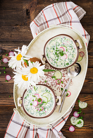 Cold soup with fresh cucumbers, radishes with yoghurt in bowl on wooden background. Traditional russian food - okroshka. Vegetarian meal. Top view. Flat lay Фото со стока