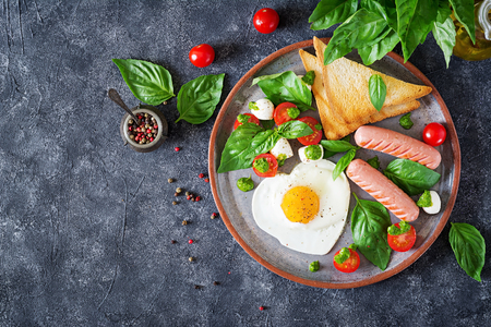 Breakfast on Valentine's Day - fried eggs in the shape heart, sausage, toast and caprese salad of a tomato, basil and mozzarella.  Homemade, tasty food. Top view. Flat lay Standard-Bild - 103929210
