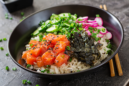 Hawaiian salmon fish poke bowl with rice, radish,cucumber, tomato, sesame seeds and seaweeds. Buddha bowl. Diet food 免版税图像