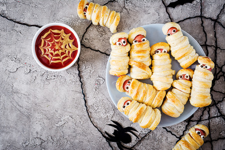 Scary sausage mummies in dough with funny eyes on table. Funny decoration. Halloween food. Top view. Flat lay