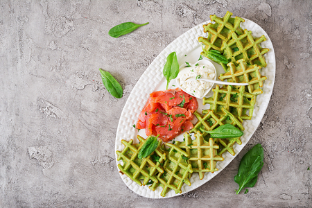 Savory waffles with spinach and cream cheese, salmon in white plate. Tasty food. Top view. Flat lay