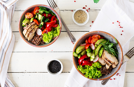 Buddha bowl dish with chicken fillet, quinoa, avocado, sweet pepper, tomato, cucumber, radish, fresh lettuce salad and sesame. Detox and healthy superfoods bowl concept. Overhead, top view, flat lay. Фото со стока