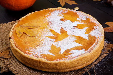 American homemade pumpkin pie with cinnamon and nutmeg, pumpkin seeds and autumn leaves on a wooden table. Thanksgiving food.
