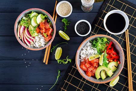 Hawaiian salmon fish poke bowl with rice, avocado, paprika, cucumber, radish, sesame seeds and lime. Buddha bowl. Diet food. Top view 免版税图像