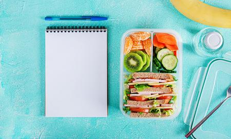 Schoollunchdoos met sandwich, groenten, water en fruit op tafel. Gezonde eetgewoonten concept. Plat leggen. Bovenaanzicht Stockfoto