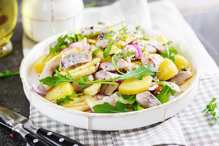 Traditional salad of salted herring fillet, fresh apples, red onion and potatoes. Kosher food. Scandinavian cuisine.