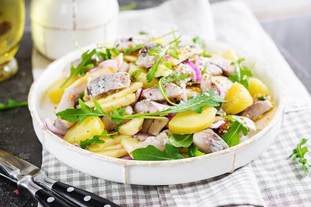 Traditionele salade van gezouten haringfilet, verse appels, rode ui en aardappelen. Kosher eten. Scandinavische keuken.